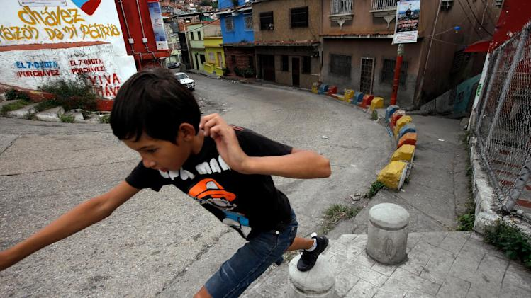 "A boy plays in front of a graffiti that reads in Spanish ""Chavez, heard of my country"" at the neighborhood of Petare in Caracas, Venezuela, Monday, Dec. 17, 2012. Smarting after a bruising loss in state elections, Venezuela's opposition will now be forced to reassess its strategy and rebuild quickly to prepare for presidential elections that many expect could be called to replace ailing leftist President Hugo Chavez. (AP Photo/Fernando Llano)"