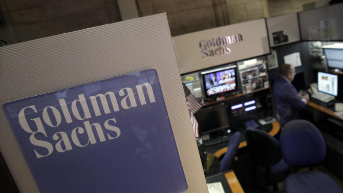 FILE - In this March 15, 2012 photo, a trader works in the Goldman Sachs booth on the floor of the New York Stock Exchange. Goldman Sachs announced Wednesday, Jan. 16, 2013 that its earnings almost tripled in the fourth quarter as investment banking revenues surged. (AP Photo/Richard Drew)
