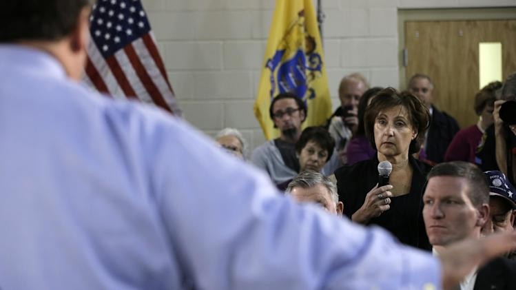 New Jersey Gov. Chris Christie answers a question from Marion Romano, second right, during a town hall meeting at Saint Mary's of The Pines Church Parish Wednesday, Jan. 16, 2013, in Manahawkin, N.J. Romano asked why she was told it might take years for the federal government to make final decisions on Advisory Base Flood Elevatiopns after Superstorm Sandy. Christie said that it was he who would make the decisions and it was only going to take him weeks, not years. (AP Photo/Mel Evans)