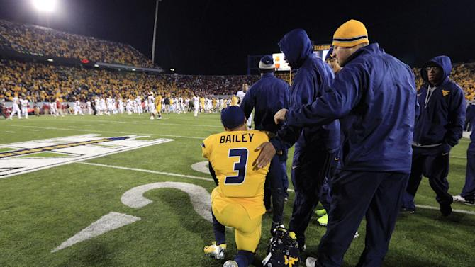 West Virginia's Stedman Bailey is consoled by teammates following their loss to Oklahoma during their NCAA college football game in Morgantown, W.Va., on Saturday, Nov. 17, 2012. Oklahoma won 50-49. (AP Photo/Christopher Jackson)