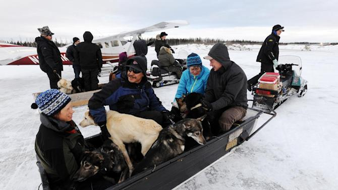 Volunteers bring dropped dogs to be loaded onto Iditarod Air Force planes and flown to McGrath during the Iditarod Trail Sled Dog Race, Wednesday, March 6, 2013, at Nikolai Airport in Nikolai, Alaska. (AP Photo/The Anchorage Daily News, Bill Roth)  LOCAL TV OUT (KTUU-TV, KTVA-TV) LOCAL PRINT OUT (THE ANCHORAGE PRESS, THE ALASKA DISPATCH)