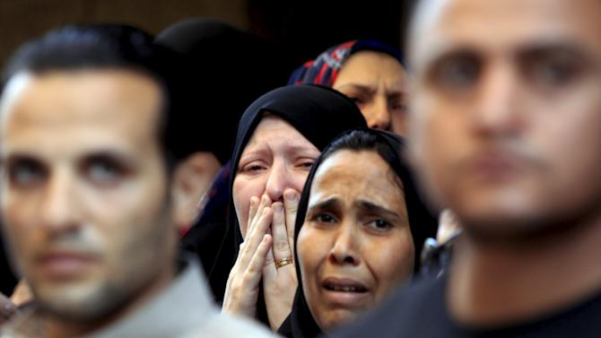 Relatives of Mohamed Adel, one of the army officers who died in yesterday's Sinai attacks, cry during the funeral in Al-Kaliobeya, near Cairo