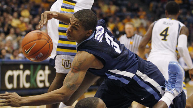 Villanova's Ty Johnson(3) crashes into Marquette's Junior Cadougan (5) during the second half of an NCAA college basketball game on Sunday, Jan. 1, 2012, in Milwaukee. Johnson was called for an offensive foul. (AP Photo/Jeffrey Phelps)