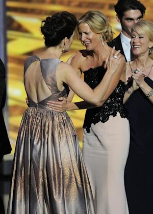 "Betsy Brandt, left, and Anna Gunn of ""Breaking Bad"" embrace on stage as they accept the award for outstanding drama series at the 65th Primetime Emmy Awards at Nokia Theatre on Sunday Sept. 22, 2013, in Los Angeles. (Photo by Chris Pizzello/Invision/AP)"
