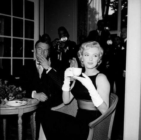 In 1956, drinking tea with Sir Laurence Olivier