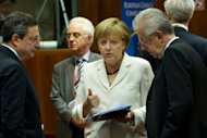 German Chancellor Angela Merkel (C) talks with European Central Bank President Mario Draghi and Italian Prime Minister Mario Monti (R) prior to a f European Union leaders summit in Brussels on June 29. The European Central Bank will pare back interest rates at a meeting Thursday to give a push to progress made by EU leaders in fighting the crisis at their summit last week, analysts predicted