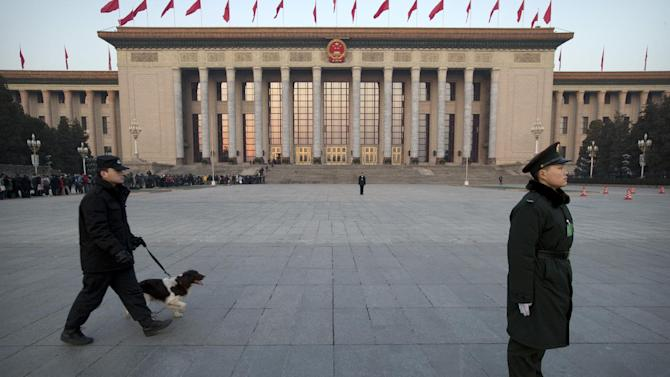 A Chinese paramilitary policeman, right, stands guard in front of the Great Hall of the People as a security officer walks past with a search dog before the opening session of the annual National People's Congress in Beijing, Thursday, March 5, 2015. China announced a lower economic growth target for this year and promised to open more industries to foreign investors as it tries to make its slowing, state-dominated economy more productive. (AP Photo/Mark Schiefelbein)