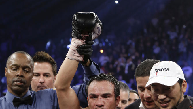 Juan Manuel Marquez, from Mexico, wears the champion's belt as his fist is raised by referee Kenny Bayless after his sixth round knockout of Manny Pacquiao, from the Philippines, in their WBO world welterweight  fight Saturday, Dec. 8, 2012, in Las Vegas. (AP Photo/Julie Jacobson)