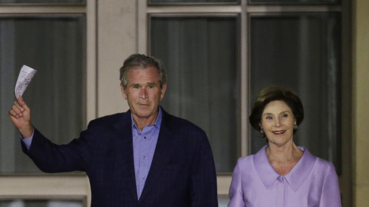 Former president George W. Bush, left, and former first lady Laura Bush enter for the lighting of Freedom Hall at the George W. Bush Presidential Center Thursday, April 25, 2013, in Dallas. (AP Photo/David J. Phillip)