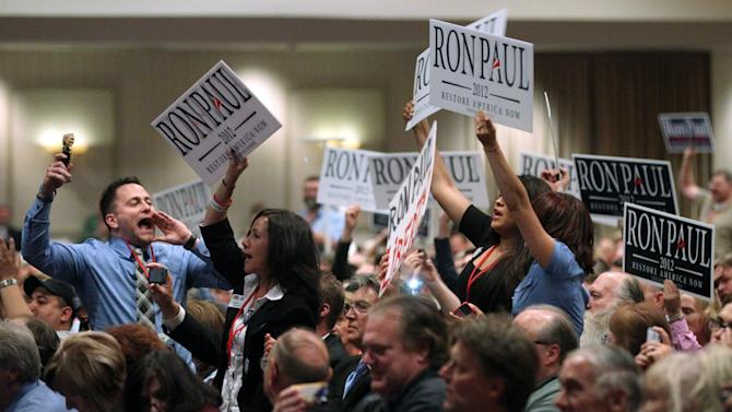 In this Saturday, May 5, 2012 photo, supporters of GOP presidential candidate Ron Paul chant his name during the Nevada Republican Party Convention in Sparks, Nev. Standing second right is Cindy Lake, acting chair of the Clark County Republican Party and a delegate to the upcoming Republican National Convention. Something's going on in America this election year: a renaissance of an ideal as old as the nation itself - that live-and-let-live, get-out-of-my-business, individualism vs. paternalism dogma that is the hallmark of libertarianism. But what looms are far larger questions about whether an America fed up with government bans and government bailouts - with government, period - is seeing a return to its libertarian roots. (AP Photo/Las Vegas Review-Journal, Cathleen Allison)