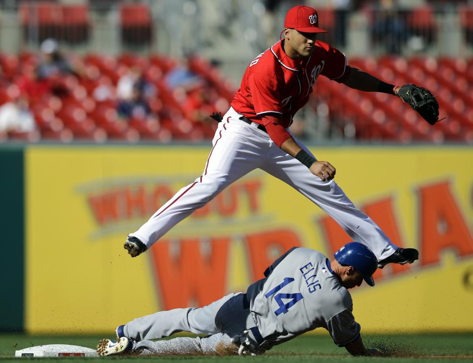 Washington Nationals shortstop Ian Desmond jumps over Los Angeles Dodgers' Mark Ellis after getting the out at second base and completing the double play during the first inning of the first baseball game of a doubleheader, Wednesday, Sept. 19, 2012, in Washington. Andre Ethier was out at first. (AP Photo/Alex Brandon)