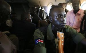 A South Sudan army soldier holds his weapon during a flight from the capital Juba to Bor town