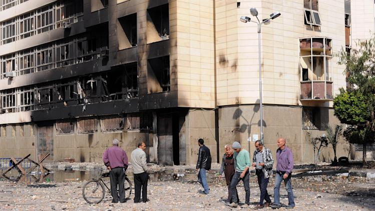 Egyptians walk past a state security office burned during clashes in Port Said, Egypt, Tuesday, March 5, 2013. Egypt's Islamist president is considering whether to give the military full control of the restive Suez Canal city of Port Said after days of deadly street clashes stoked by excessive use of force by riot police, officials said Tuesday. (AP Photo)