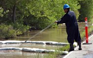 A contractor for ExxonMobil tends to an oil containment boom along the Yellowstone River near Laurel, Mont., after a pipeline that runs under the river ruptured Saturday July 2, 2011. The pipeline break was contained early Saturday morning but the spill stretched over dozens of miles. (AP Photo/Matthew Brown)
