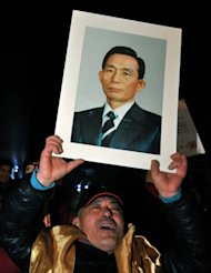 <p>A supporter of Park Geun-Hye is pictured holding a portrait of her father Park Chung-Hee on December 20, 2012. Park Chung-Hee ruled South Korea with an iron fist for 18 years until his eventual assassination, and remains a divisive figure.</p>