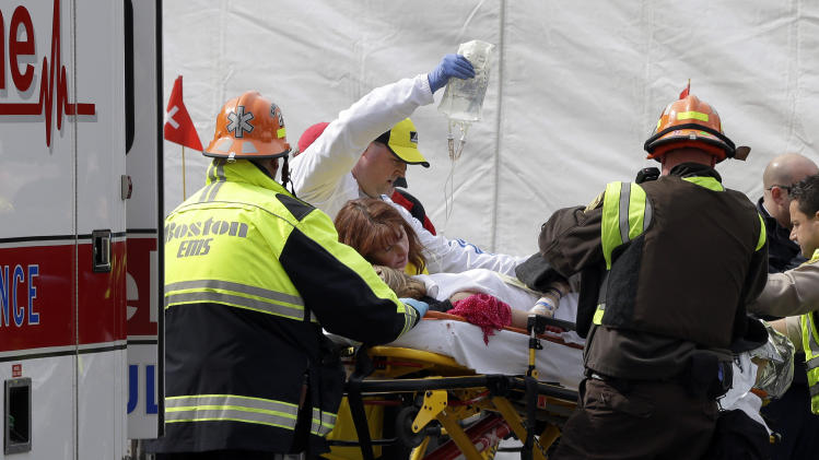 An injured person is loaded into an ambulance in the aftermath of two blasts which exploded near the finish line of the Boston Marathon in Boston Monday, April 15, 2013. Two bombs exploded near the finish line of the Boston Marathon on Monday, killing two people, injuring 23 others and sending authorities rushing to aid wounded spectators. A senior U.S. intelligence official said two other explosive devices were found nearby.  (AP Photo/Elise Amendola)