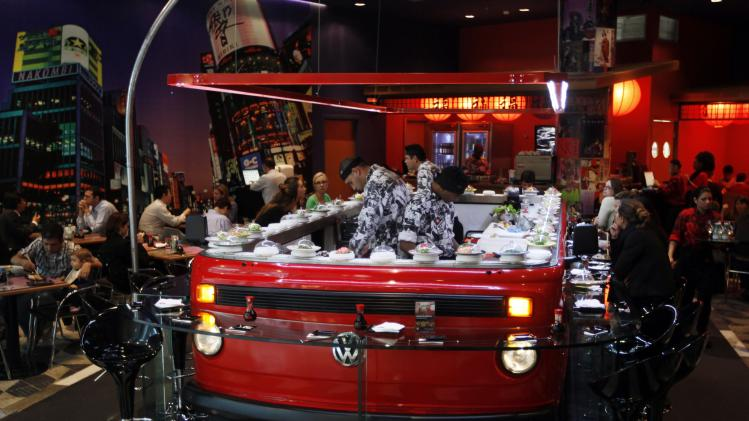 People eat near a sushi bar adapted inside a Volkswagen Kombi minibus in Sao Paulo
