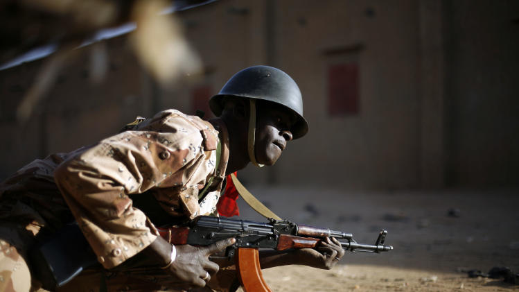 A Malian soldier takes cover behind a truck during exchanges of fire with jihadists in Gao, northern Mali, Sunday, Feb. 10, 2013. (AP Photo/Jerome Delay)