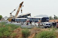 <p>A crane lifts the mangled remains of a coach of the Bangalore-bound Hampi Express after it collided with a stationary goods train near Penneconda town in Ananthpur District, about 145 kms from Bangalore on Tuesday. At least 19 people were killed and 36 injured in the collision.</p>