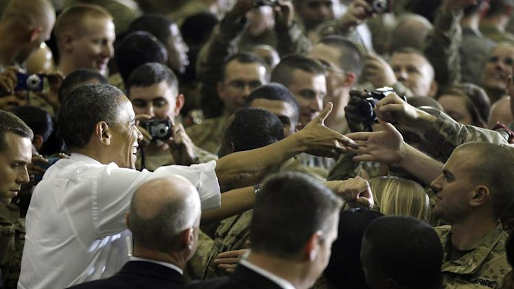 """FILE -In this May 2, 2012 file photo, President Barack Obama greets troops at Bagram Air Field, Afghanistan. As slogans go, President Barack Obama's promise of the """"light of a new day"""" in Afghanistan isn't as catchy as the """"Mission Accomplished"""" banner that hung across the USS Abraham Lincoln the day President George W. Bush announced the end of major combat operations in Iraq. (AP Photo/Charles Dharapak, File)"""