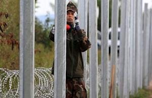 Soldiers build a barbed wire fence at the Hungary-Croatia…
