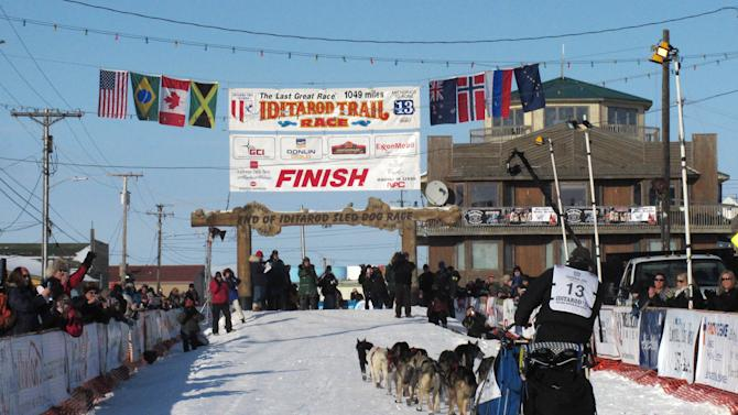 FILE - In this March 13, 2013, file photo, residents greet Kotzebue musher John Baker as he nears the finish line in Nome, Alaska. If you want to see mushers cross the finish line at the world's most famous sled dog race in March 2014, better make your reservations soon. There aren't many hotel rooms available at the end of the Iditarod Trail Sled Dog Race in Nome, leaving mushers and their families battling with fans, tourists and volunteers for a place to sleep. (AP Photo/Mark Thiessen, file)