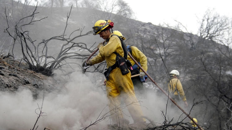 Firefighter James Heaton, front,  hoses down hotspots in the Angeles National Forest Wednesday Sept. 5, 2012 near Los Angeles. Fire crews are getting help from rain in battling a 3,800-acre fire in the San Gabriel Mountains northeast of Los Angeles. (AP Photo/Nick Ut)