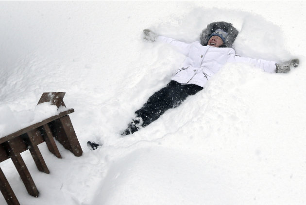Nicole Lacoursiere of North Andover, Mass. falls back to make a snow angel Saturday, Feb. 9, 2013 in some 24 inches of snow that had fallen in her yard. A behemoth storm packing hurricane-force wind g