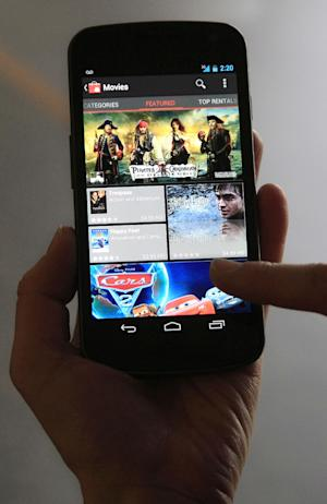 An Associated Press reporter demonstrates the Samsung Galaxy Nexus phone, which runs the newest version of Google's Android mobile software, Ice Cream Sandwich, during a product review in San Francisco, Tuesday, Dec. 13, 2011. (AP Photo/Jeff Chiu)