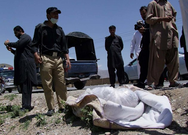 Pakistani security officials stand next to covered body of British Red Cross worker Khalil Rasjed Dale at the site in Quetta, Pakistan on Sunday, April 29, 2012.  The body of a British Red Cross worke
