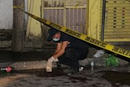 A Philippino policeman gathers evidence at the blast site after a unidentified man tossed an explosive device into a crowded tourist area in Iligan City, in sourthern island of Mindanao on Saturday. Philippine President Benigno Aquino promised Sunday security forces would arrest the culprits behind a grenade attack that left two people dead and at least 19 others hurt in the troubled south