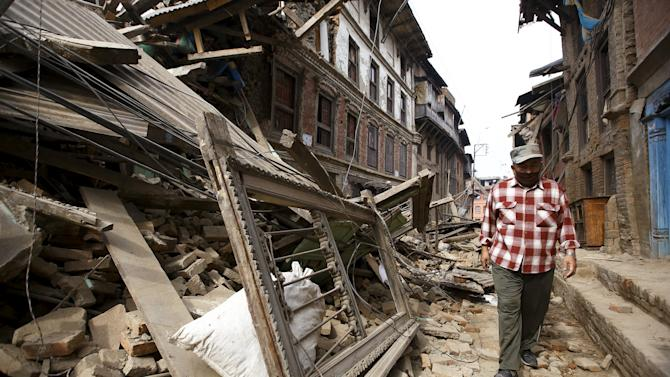 Man walks along damaged houses a day after an earthquake in Bhaktapur