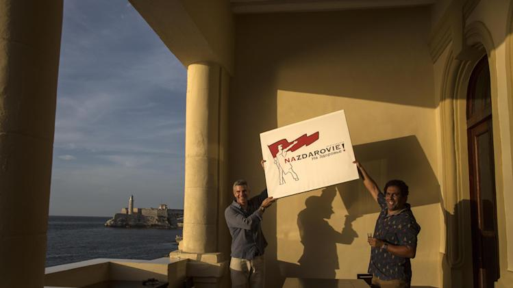 """In this Aug 20, 2014 photo, Gregory Biniowsky, left, and business partner Yociel Marrero pose with their new restaurant's sign on the terrace of their new eatery, Nazdarovie, that overlooks the ocean in Havana, Cuba. """"The idea with Nazdarovie is really to celebrate a unique social and cultural link that existed and to a certain degree still exists today between Cuba of 2014 and what was once the Soviet Union,"""" said Biniowsky, a lawyer and consultant who has lived in Havana for the last two decades. (AP Photo/Ramon Espinosa)"""