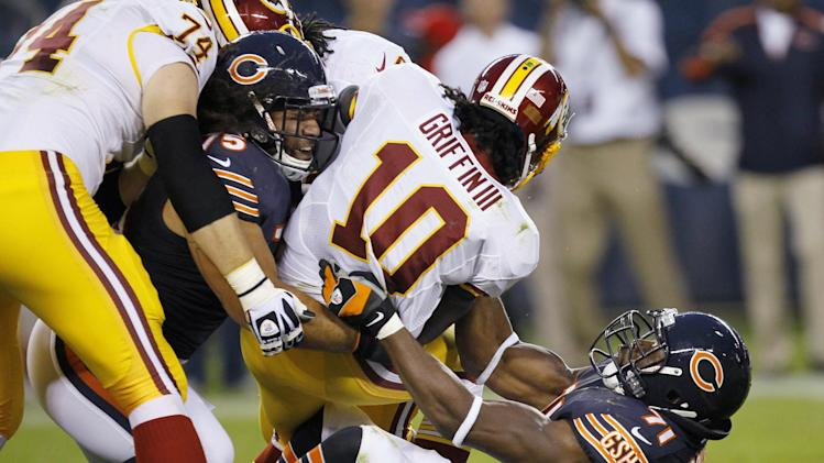 Washington Redskins quarterback Robert Griffin III (10) is tackled by Chicago Bears defensive end Israel Idonije (71) and defensive tackle Matt Toeaina (75) during the first half of an NFL preseason football game in Chicago, Saturday, Aug. 18, 2012. At left is Redskins offensive tackle Tyler Polumbus. (AP Photo/Charles Rex Arbogast)