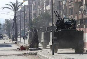 Lebanese army soldiers ride on their military vehicles in Tripoli