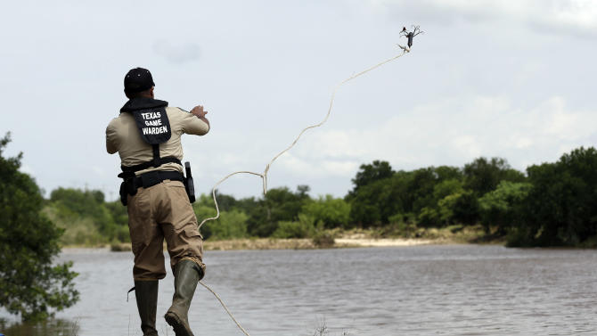 Members of the Texas Parks and Wildlife use a grappling hook to search Sunday, May 26, 2013, in Shertz, Texas, for a missing teen who was swept away in a rain swollen Cibilo Creek Saturday. (AP Photo/Eric Gay)
