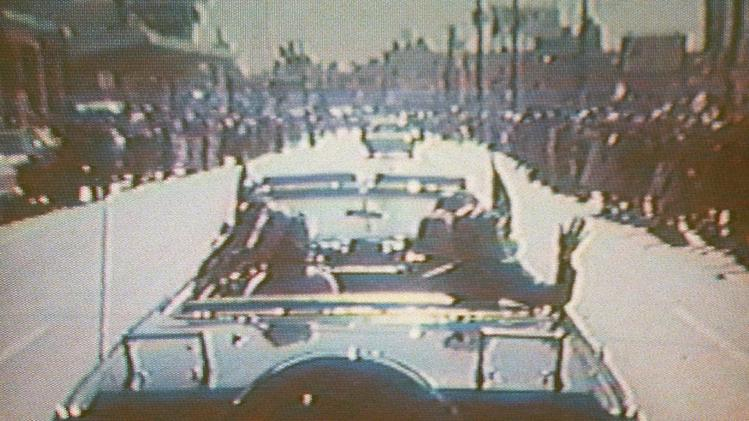 FILE - In this footage taken by presidential aide Dave Powers and photographed from a television screen, President John F. Kennedy, accompanied by his wife, Jacqueline, waves from his limousine in Dallas on Nov. 22, 1963. According to an AP-GfK survey done in April 2013, about 6 in 10 Americans say they believe multiple people were involved in a conspiracy to assassinate President John F, Kennedy, while only one-fourth think Oswald acted alone. Belief in a conspiracy, though strong, has declined since a 2003 Gallup poll found 75 percent said they thought Oswald was part of a wider plot. The Powers film, uncovered by the Assassination Records Review Board and released Thursday, Nov. 21, 1996, shows Kennedy's trip to Texas Nov. 21-22, 1963, prior to the assassination. Powers ran out of film before the motorcade entered Dealey Plaza where the fatal shots where fired. (AP Photo/Assassination Records Review Board, Dave Powers)
