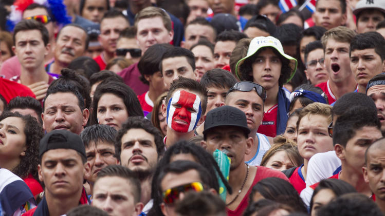Costa Rican's soccer fans watch the World Cup round of 16 match on TV against Greece in San Jose, Costa Rica, Sunday, June 29, 2014. (AP Photo/Esteban Felix)