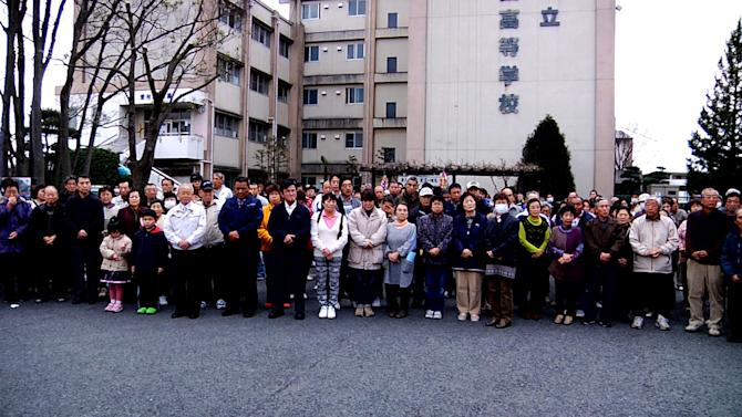 """In this image made from promotional footage for the film """"Nuclear Nation"""" released by the 2012 Documentary Japan, Big River Films, Futaba mayor Katsutaka Idogawa, sixth from left in white jacket, poses with evacuees from Futaba town in front of their shelter, the abandoned Kisai high school, in Kazo, Saitama prefecture, near Tokyo, on March 11, 2012, a year after the tsunami and earthquake hit northern Japan. The film """"Nuclear Nation,"""" directed by Atsushi Funahashi, documented a story of the residents of Futaba, the town where the tsunami crippled Fukushima Dai-ichi nuclear power plant is located. The March 2011 catastrophe in Japan has set off a flurry of independent films telling the stories of regular people who became overnight victims, stories the creators feel are being ignored by mainstream media and often silenced by the authorities. Nearly two years after the quake and tsunami disaster, the films are an attempt by the creative minds of Japan's movie industry not only to confront the horrors of the worst nuclear disaster since Chernobyl, but also as a legacy and to empower the victims by telling their story for international audiences. (AP Photo/2012 Documentary Japan, Big River Films) CREDIT MANDATORY, EDITORIAL USE ONLY"""