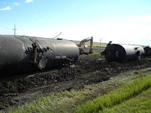 Derailed oil tanker cars lie off track near Culbertson,…