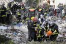 Firefighters carry a body found in the rubble of a four-storey residential building that collapsed following a blast in Rosny-sous-Bois in the eastern suburbs of Paris on August 31, 2014