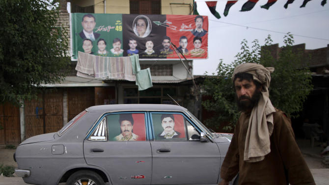 In this Tuesday, May 7, 2013, photo, a Pakistani man walks by a car decorated with posters showing members of the Pakistan People's Party (PPP), and backdropped by a banner showing candidates from the PPP for the upcoming parliamentary elections, in a neighborhood in Islamabad, Pakistan. The campaign posters, fliers and commercials for the Pakistan People's Party are both advertisements for why the party has been so popular and indicate the challenges it faces in the May 11 election: two of the people on the posters are dead and another is not old enough to run in the election. (AP Photo/Muhammed Muheisen)