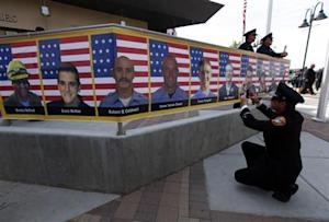 San Diego firefighter Bunsoldat takes a picture of each of the Prescott Fire Department's Granite Mountain Hotshots team from a banner that circles the entrance to their memorial in Prescott Valley, Arizona