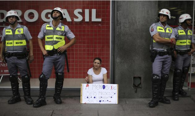A member of Brazil's MTST smokes a cigarette while holding a placard near military policemen during a protest to demand for affordable low-income housing from the government in Sao Paulo