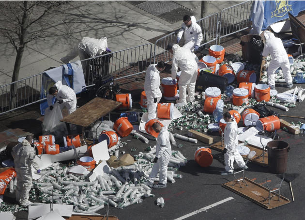 Investigators comb through the post finish line area of the Boston Marathon at Boylston Street, two days after two bombs exploded just before the finish line, Wednesday, April 17, 2013, in Boston. (AP