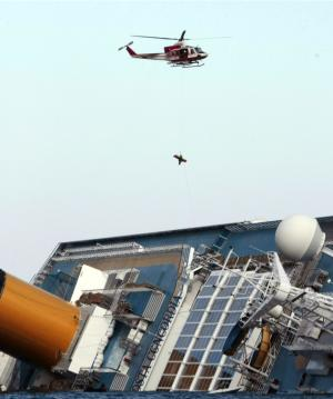 An Italian firefighter helicopter airlifts a rescued passenger from the luxury cruise ship Costa Concordia which ran aground off the tiny Tuscan island of Giglio, Italy, Sunday, Jan. 15, 2012. Firefighters worked Sunday to rescue a crew member with a suspected broken leg from the overturned hulk of the luxury cruise liner Costa Concordia, 36 hours after it ran aground. More than 40 people are still unaccounted-for. (AP Photo/Gregorio Borgia)