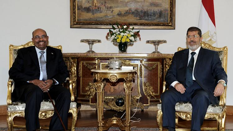 In this image released by the Egyptian President, Egyptian President Mohammed Morsi, right, meets with Sudan's President Omar al-Bashir at the Presidential Palace in Cairo, Egypt, Sunday, Sept. 16, 2012. Al-Bashir met on Sunday with his Egyptian counterpart in Cairo, defiant of the International Criminal Court's two arrest warrants against him for an alleged role in his country's turbulent western Darfur region. (AP Photo/Egyptian Presidency)