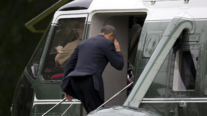 President Barack Obama salutes at the top of the step as he boards Marine One on the South Lawn of the White House, Friday, May 24, 2013, in Washington. President Obama forgot to salute the Marine at the base of the steps as he boarded so he came back out to shake hands with him. President Obama is traveling to Annapolis to deliver the commencement address at the United States Naval Academy (AP Photo/Carolyn Kaster)