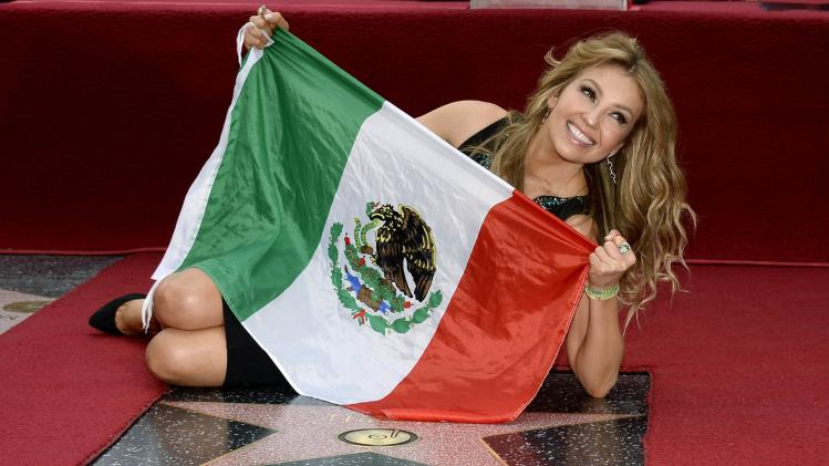 Mexican singer-songwriter Thalia holds up her national flag as she poses on her star after it was unveiled on the Hollywood Walk of Fame in Hollywood, California