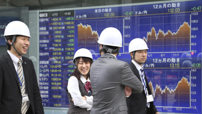 Office workers wearing helmets walk by an electronic stock board of a securities firm during their disaster drill in Tokyo Thursday, Feb. 13, 2014. Asian stocks were mostly lower Thursday, led by a fall in Tokyo after Wall Street ended lower for the first time this week. Japan's Nikkei 225, the region's main index, dropped 265.32 points, or 1.79 percent to 14,534.74. (AP Photo/Koji Sasahara)
